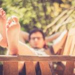 Mann liegt entspannt auf Holzbank, Fe im Vordergrund, retro
